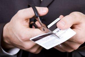 Мужчина разрезает банковскую карточку